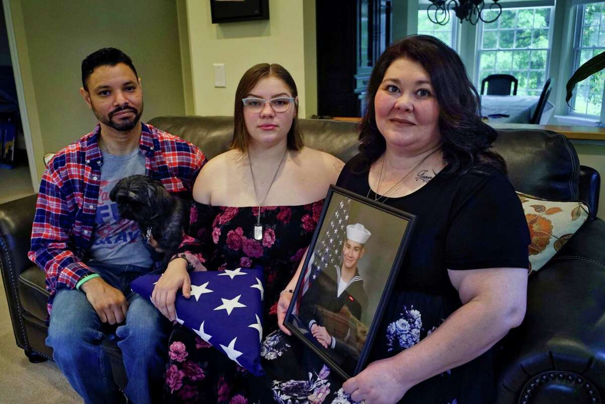 Michael and Jolee Hicks pose with their daughter Sienna, center, at their Capital Region home on Tuesday, June 18, 2019. Jolee Hicks is holding a photo of their son, Macoy, who killed himself while in a military brig. Sienna holds the flag from Macoy's funeral. (Paul Buckowski/Times Union)