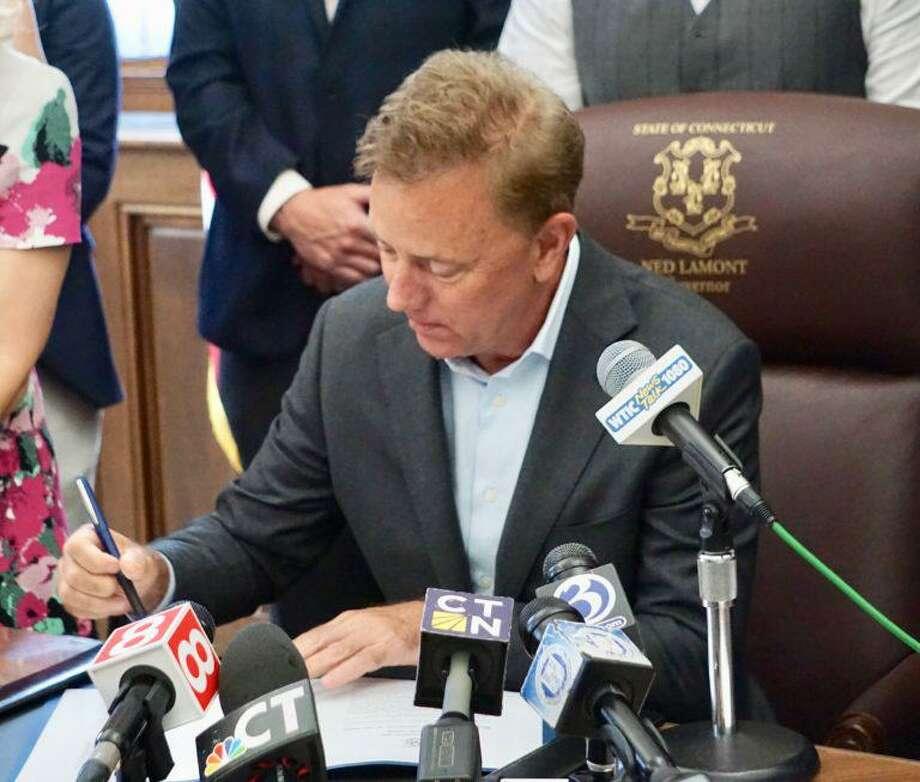 Gov. Ned Lamont signs a ceremonial copy of an HIV prevention bill. Photo: Mark Pazniokas / CTMirror.org