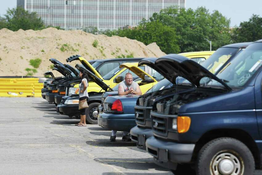 People look at various cars during the NYS Office of General Services auction on Wednesday, July 10, 2019 at Harrimon Campus in Albany, NY. (Phoebe Sheehan/Times Union)