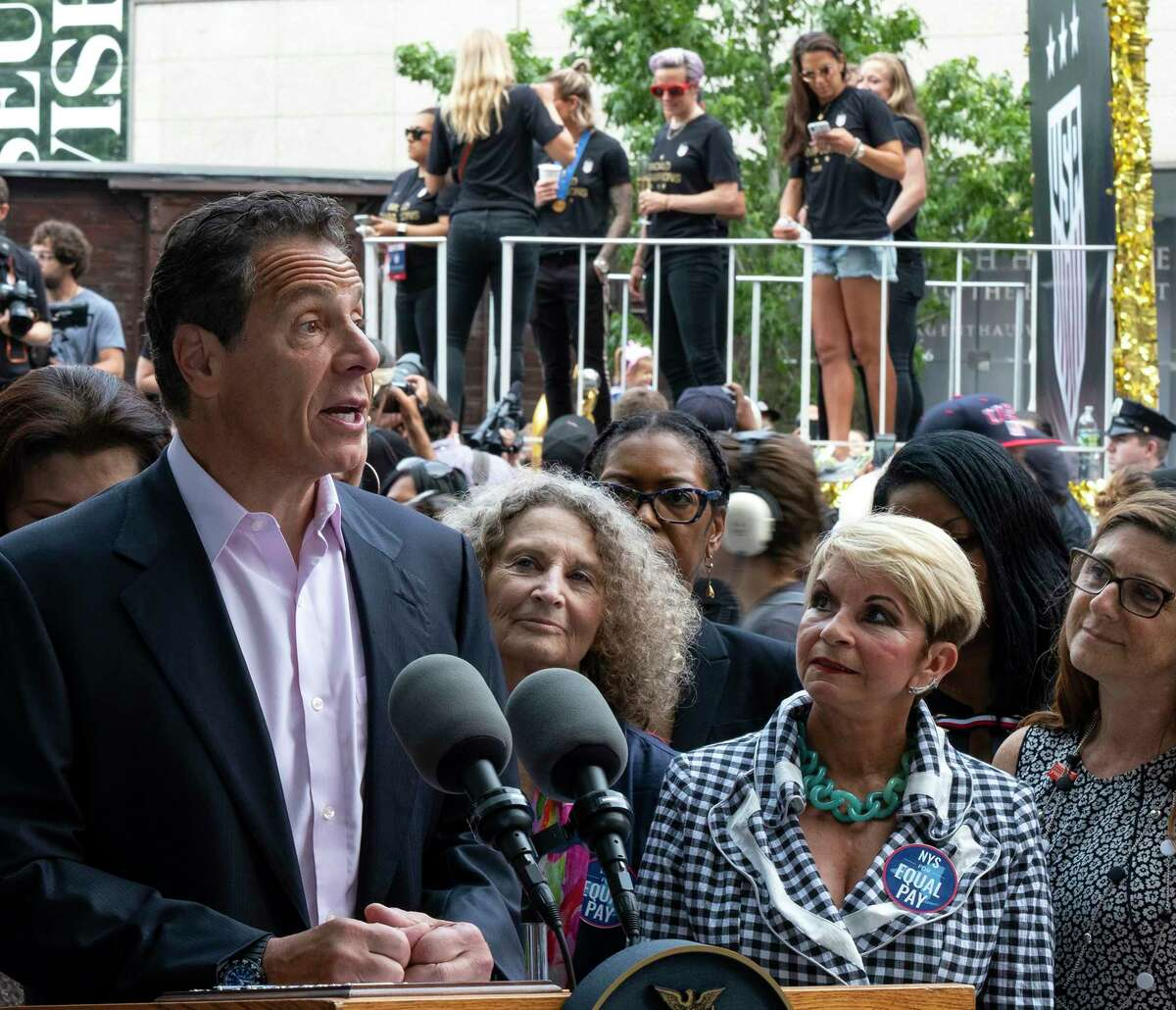 With members of the U.S. women's soccer team in the background before the start of a ticker tape parade in their honor, Gov. Andrew Cuomo speaks before signing a bill into law Wednesday, July 10, 2019, in New York. The bill will expand a law banning gender pay discrimination to make it illegal for employers to pay workers differently based on their age, race, religion or other characteristics, and making it easier for workers to prove pay discrimination in court.