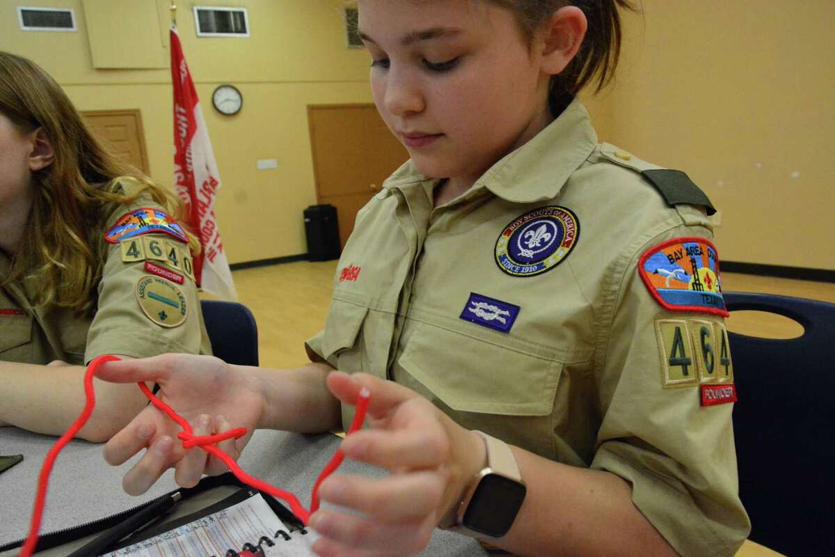 Troop 4640 member Madeleine Clark practices tying knots. Members of the all-girl troop say they are eager to learn skills related to camping and other outdoor skills.