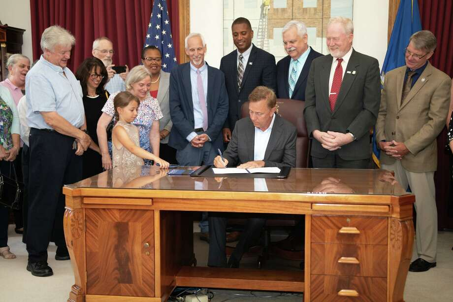 State Sen. Norm Needleman, D-Essex, (to Gov. Ned Lamont's immediate right) joined a coalition of political and regional leaders as Lamont signed legislation into effect better protecting Connecticut waterways from invasive species. Photo: Contributed Photo