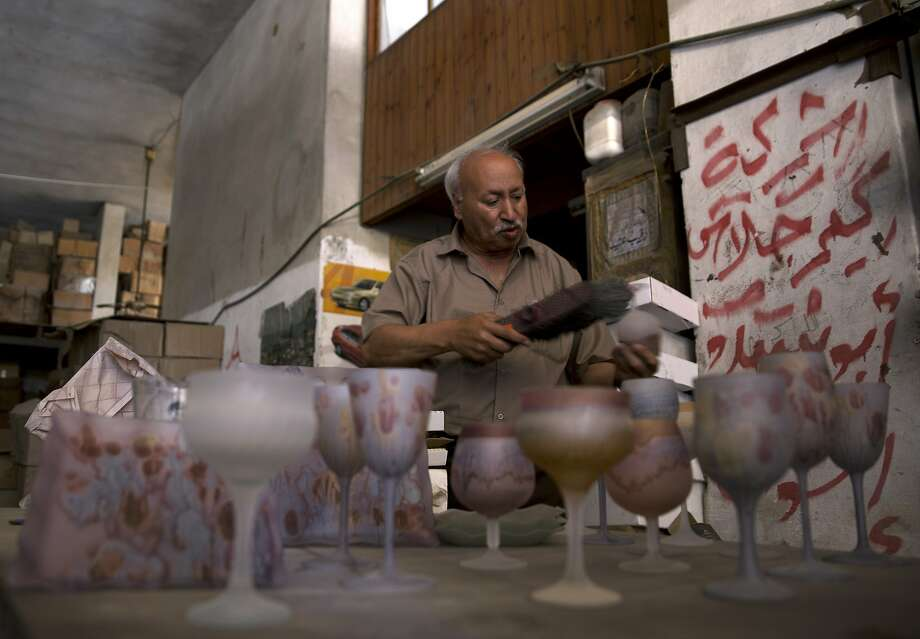 Abed Abu Sido removes the dust from hand-painted glasses at his factory that has been closed since 2008. In his heyday, he had 15 employees and took part in exhibitions in Europe. Photo: Khalil Hamra / Associated Press