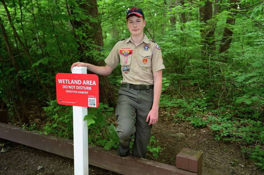 Life Scout Ryan Doyle with signs he had created for his Eagle Scout Project on Saturday, July 6, 2019, at Crabury Park in Norwalk. Doyle chose to protect the wetlands in Norwalk as his Eagle project. His project was to design and install signs in Cranbury Park that identify the wetland areas. He included a different QR code on each sign, so the park visitors can use their cell phones to scan the codes to get more information about wetland conservation. Photo: Erik Trautmann / Hearst Connecticut Media / Norwalk Hour