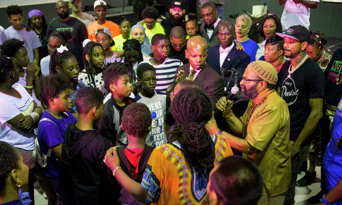 """Community members surround a group of children to end a gathering of community activists speaking out against violence against children, at the SHAPE Community Center in Houston, Tuesday, July 9, 2019. The group called for a """"Cease Fire"""" in the wake of many recent deaths of children."""