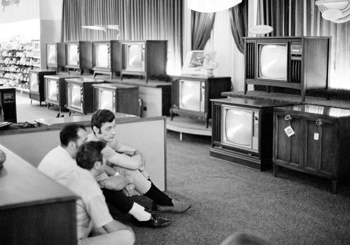 In this July 16, 1969 file photo, people watch the Apollo 11 Saturn V rocket launch on multiple TV's at a Sears department store in White Plains, N.Y.