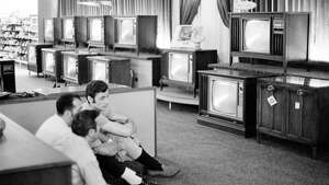 ADVANCE FOR USE SATURDAY, JULY 13, 2019 AND THEREAFTER-FILE - In this July 16, 1969 file photo, people watch the Apollo 11 Saturn V rocket launch on multiple TV's at a Sears department store in White Plains, N.Y.