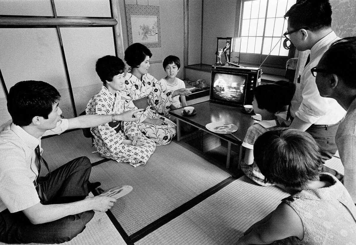 In this July 21, 1969 file photo, a family in Tokyo watches TV showing U.S. President Richard Nixon superimposed on a live broadcast of the Apollo 11 astronauts saluting from the moon.