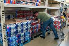 Fernando Lorenzo grabs four cases of water at the Montrose Market H-E-B on West Alabama Street during his lunch break, Wednesday, July 10, 2019.