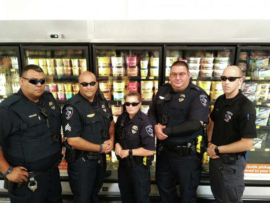 Members of the Cibolo Police Department pose for a photo in front of the ice cream aisle, jokingly pretending to prevent Blue Bell lickers. Photo: Facebook: Cibolo Police Deaprtment