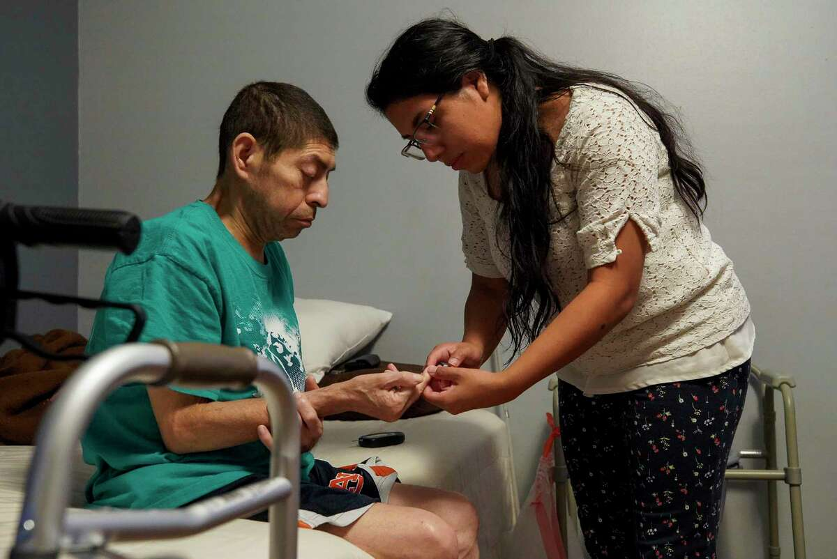 Lorena Argueta takes her father's sugar blood levels right after they wake up every morning Friday, July 5, 2019, in Houston. Argueta is the primary care taker for her father, who is blind due to the cataracts caused by diabetes, and has kidney failure.