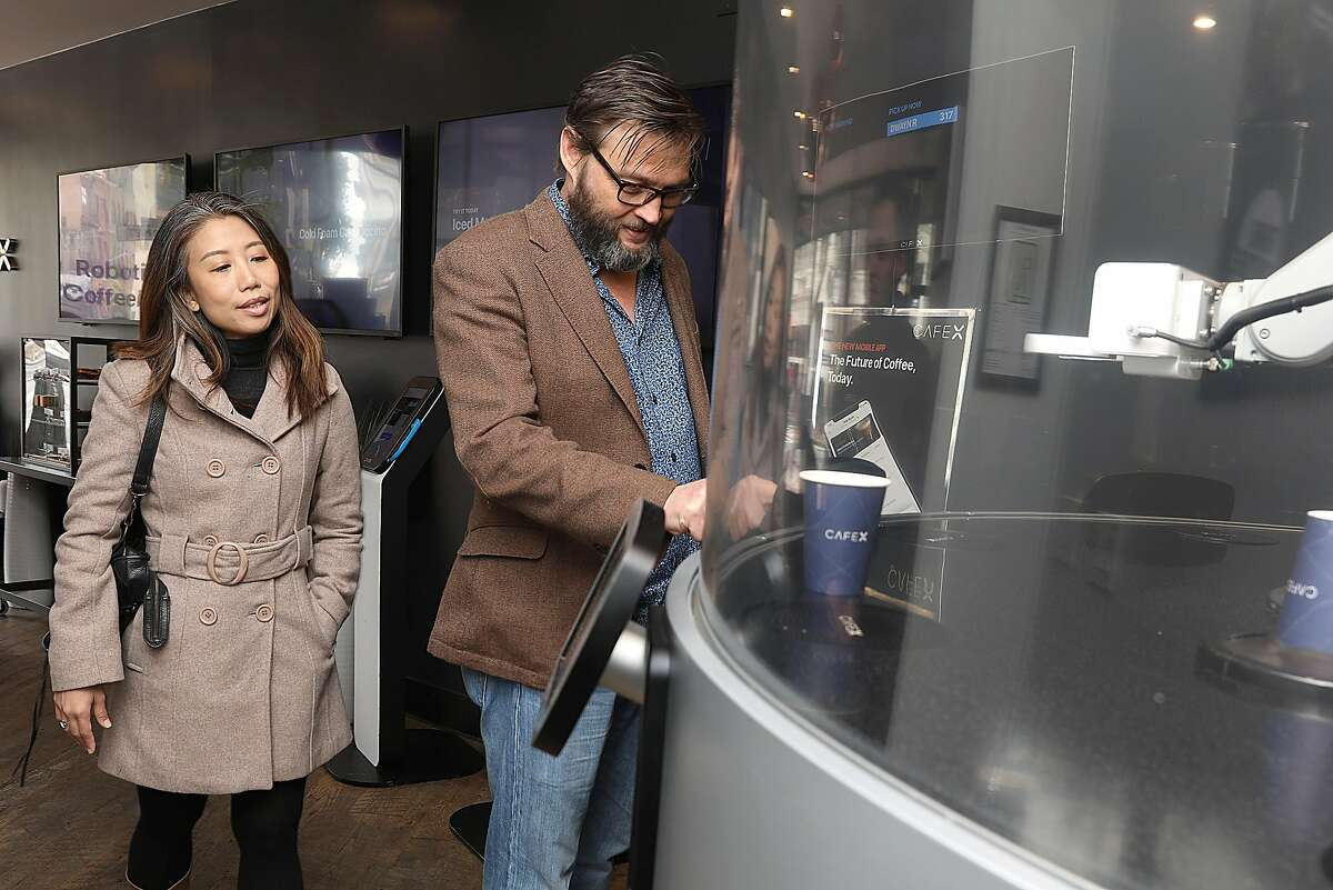 Dwayne (cq) and his wife Sandy Lythgo from Singapore have a robot made Flat White coffee at Cafe X on Friday, March 8, 2019, in San Francisco, Calif.