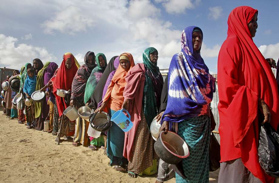 Somali women fleeing drought line up in May to receive food at a camp outside the capital, Mogadishu. Photo: Farah Abdi Warsameh / Associated Press
