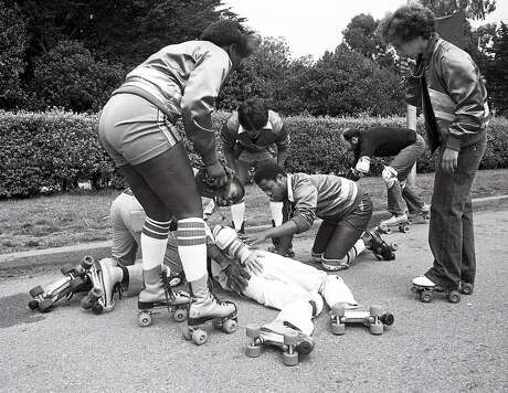 Aug. 10, 1980: Skate Patrol members Rosalinda Gonzalez and David Miles Jr. help a fallen roller skater in Golden Gate Park in 1980. Photo: Frederic Larson / The Chronicle 1980