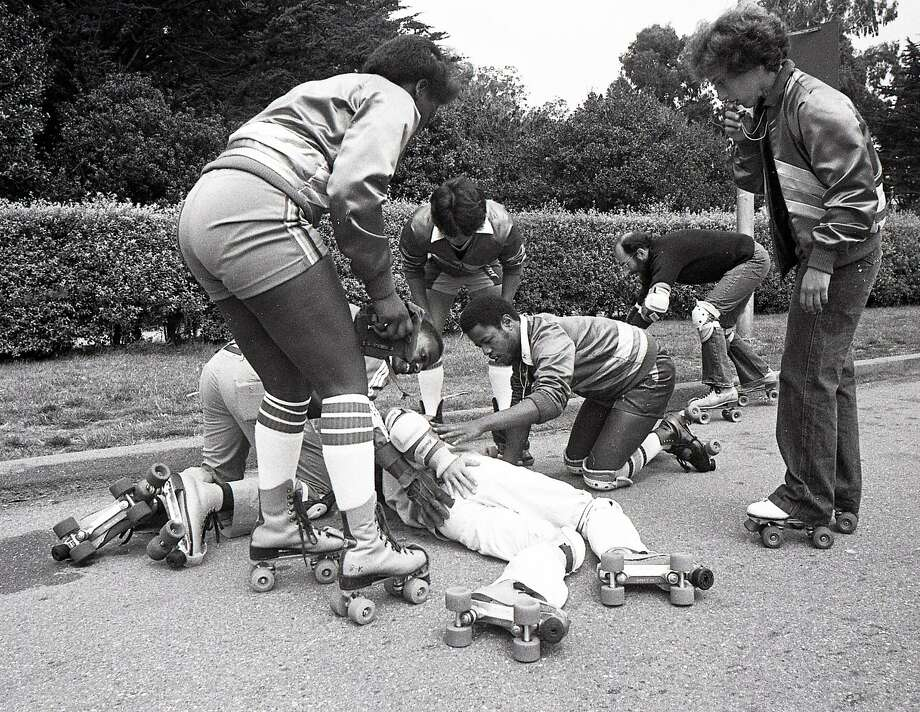 Aug. 10, 1980: Skate Patrol members Rosalinda Gonzalez and David Miles Jr. help a fallen roller skater in Golden Gate Park in 1980. Photo: Frederic Larson / The Chronicle