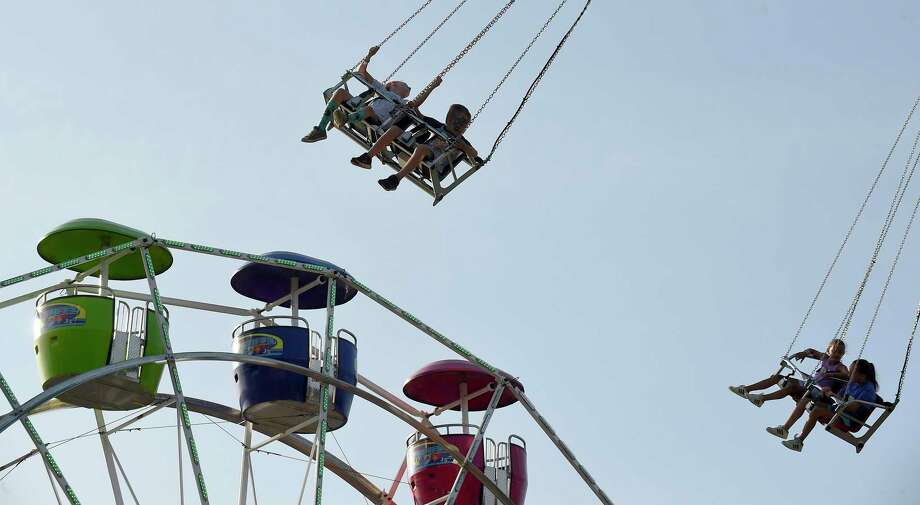 Carnival goers enjoy a high flying swing ride during The Parish of St. Catherine of Sienna and St. Agnes annual Carnival of Fun at St. Catherine of Siena in Greenwich, Conn. on July 9, 2019. Photo: Matthew Brown / Hearst Connecticut Media / Stamford Advocate