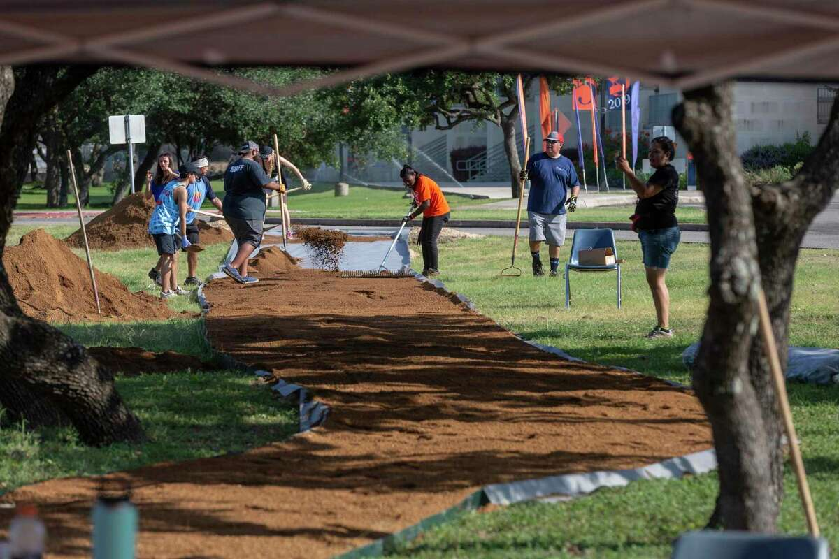 Volunteers work to construct a 300-foot-long crushed granite trail Wednesday at the new Tito Bradshaw Bicycle Shop on the UTSA Main Campus. Bradshaw was a well-known San Antonio cyclist who died last spring after being struck by a car while riding his bike.