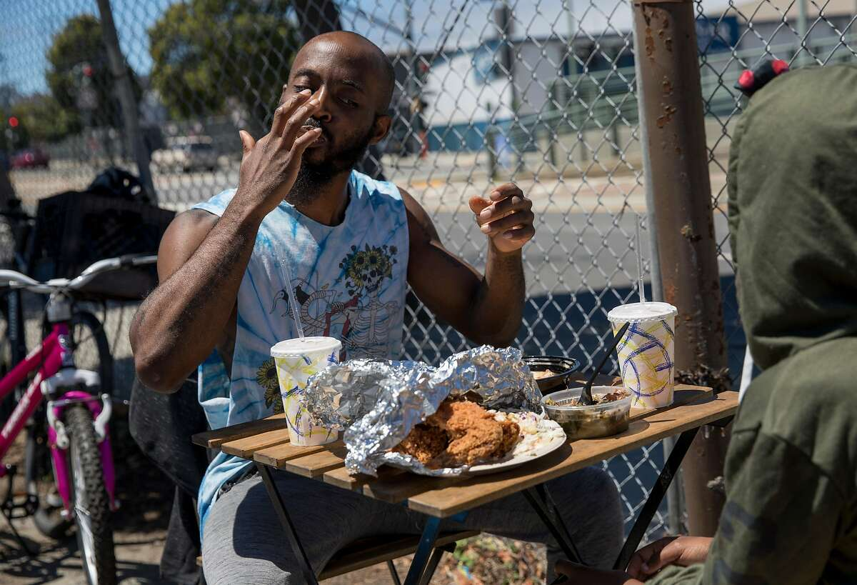 Maurice Hightower of San Francisco eats lunch from Soul Bowl'z with his daughter Imani Hightower, 12, at the Bayview Bistro food truck park in the Bayview district of San Francisco, Calif. Wednesday, July 10, 2019.