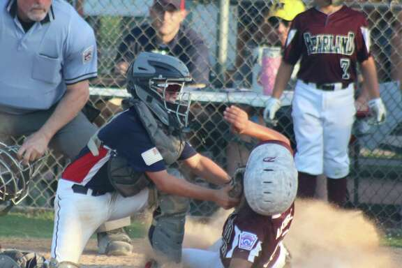 Pearland East's Eziekiel Alkire is tagged out at home plate by Bayside catcher Wilson Reagan, preventing East from going up 2-0 in the second inning Tuesday night.