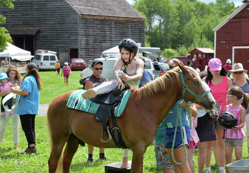 Eleven-year-old Zohara Tourjman of Rotterdam mounts a pony during CanalFest at Mabee Farm Saturday July 15, 2017 in Rotterdam Junction, NY. (John Carl D'Annibale / Times Union)