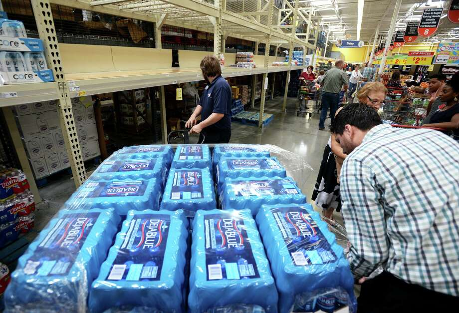 Chris Reynolds, left, and David Rodriguez haul pallets of bottled water to restock shelves at Beaumont's H-E-B as customers stock up on storm preparations Wednesday.   Photo taken Wednesday, 7/10/19 Photo: Guiseppe Barranco/The Enterprise, Photo Editor / Guiseppe Barranco ©