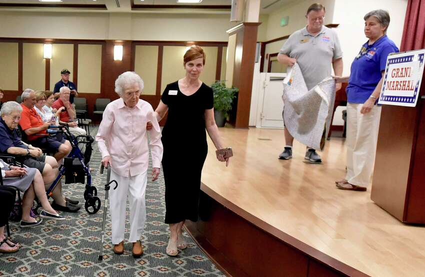 Hamden, Connecticut - Wednesday, July 10, 2019: Captain Celine Finn, 91, U.S. Navy retired, of Hamden, left, who served as a nurse during the Vietnam War, the Korean War and in the Mediterranean after she worked as a nurse at the former Hospital of St. Raphael in New Haven, led to the stage by Maria L. Freda, Whitney Center Director of Resident Services, second from left, before receives the