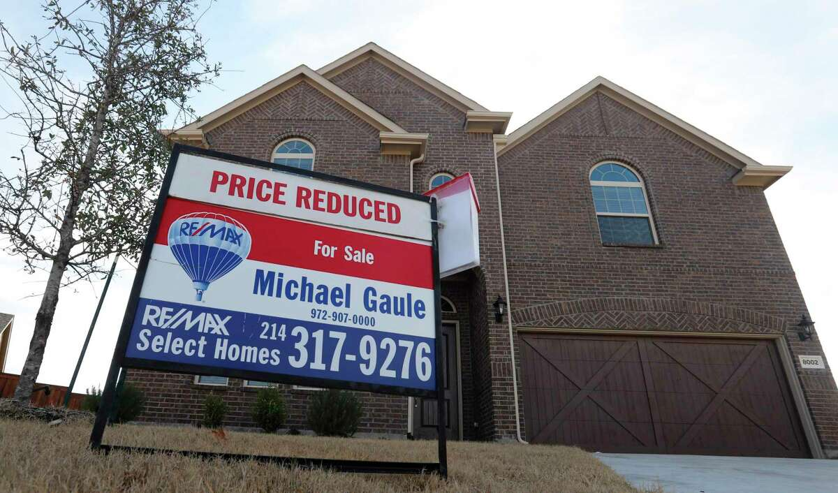 In this Wednesday, Feb. 20, 2019, photo a price reduced for sale sign sit in front of a home in north Dallas. On Thursday, May 30, Freddie Mac reports on this week's average U.S. mortgage rates. (AP Photo/LM Otero, File)