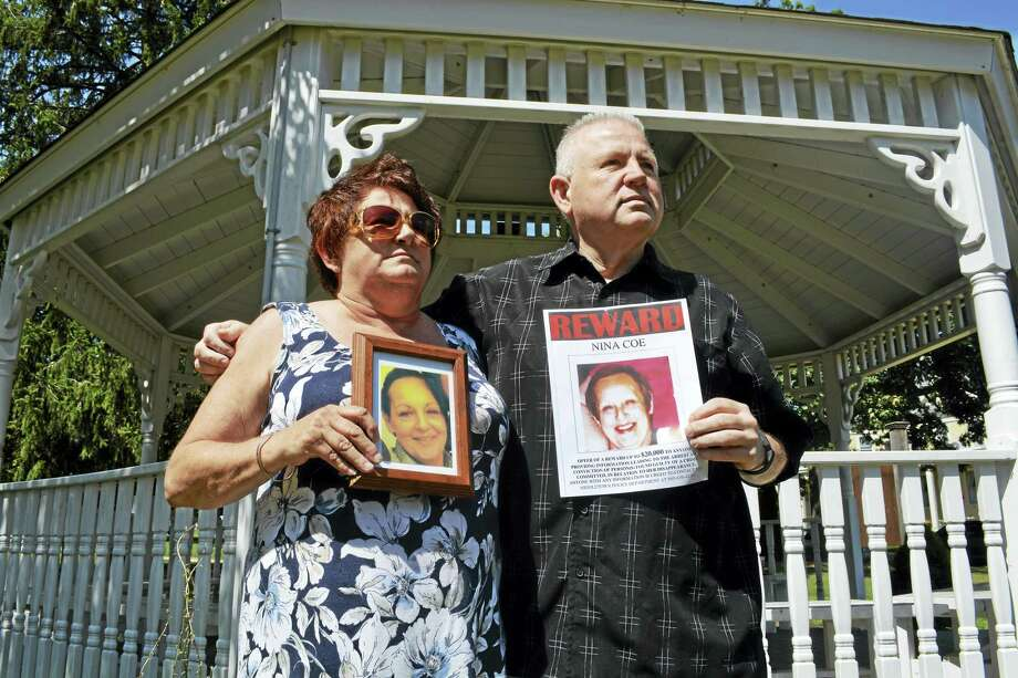Dale Ocelik, left, holds a framed photograph of her big sister Nina Coe as Coe's younger brother Michael Plourde displays the poster the family put up all over town when the 56-year-old disappeared in July 2015. Plourde is hosting a candlelight vigil Sunday at 5 p.m. on the South Green on Main Street in Middletown. Photo: Hearst Connecticut Media File Photo