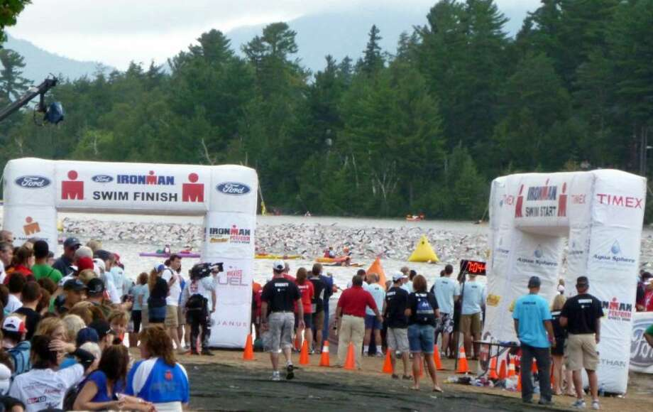 Swimmers create a frenzy in the water as they begin the first test in the Ironman triathlon at Lake Placid last Sunday.  Photos are contributed by Barbara Davis of Bethel. Photo: Contributed Photo / The News-Times Contributed