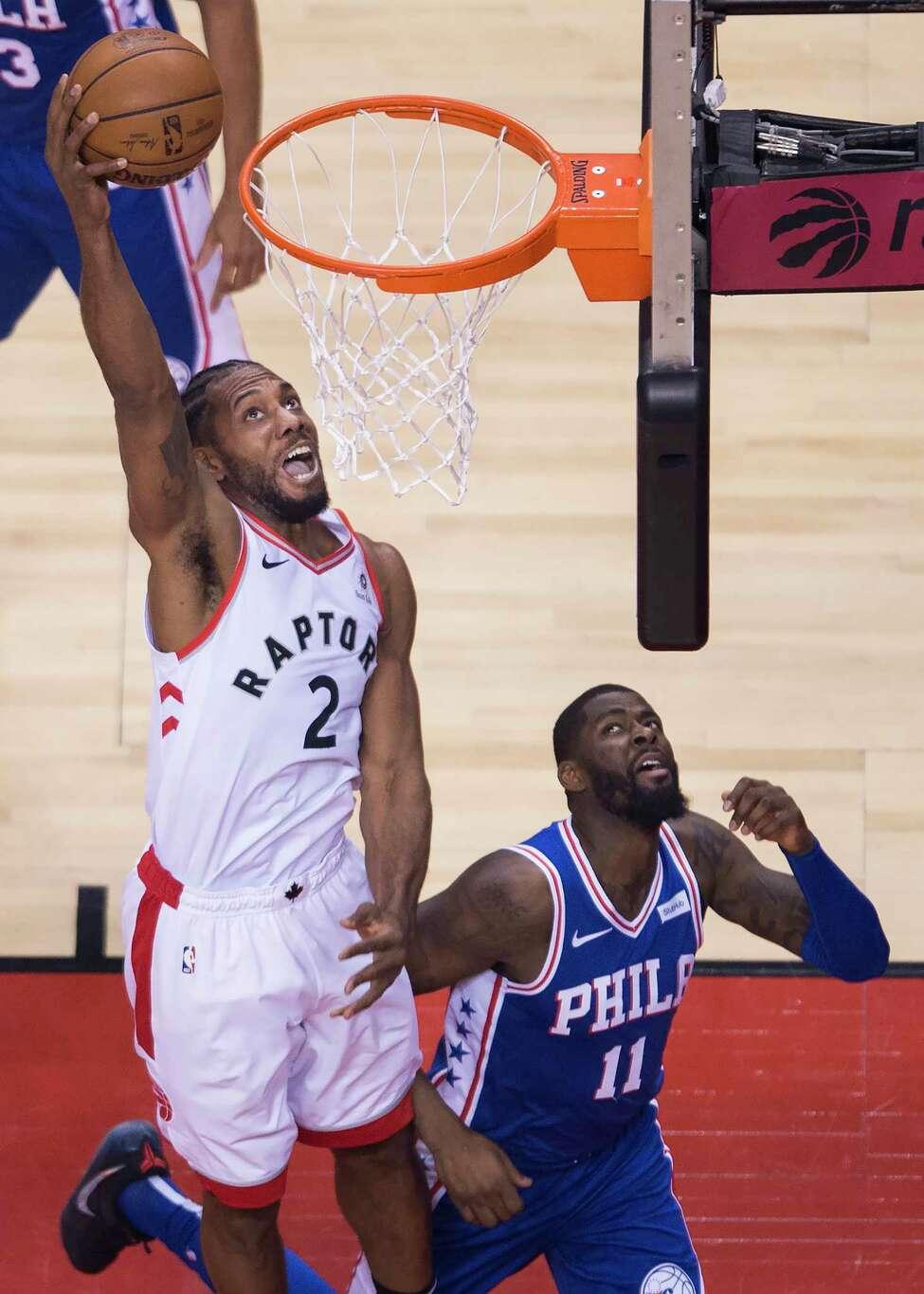 Toronto Raptors forward Kawhi Leonard (2) slam-dunks past Philadelphia 76ers forward James Ennis III (11) during the first half of Game 1 of a second-round NBA basketball playoff series in Toronto, Saturday, April 27, 2019. (Nathan Denette/The Canadian Press via AP)