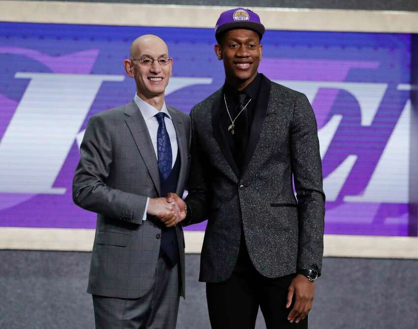 FILE - In this Thursday, June 20, 2019, file photo, Virginia's De'Andre Hunter, right, is greeted by NBA Commissioner Adam Silver after being selected with the fourth pick overall by the Los Angeles Lakers during the NBA basketball draft in New York. Hunter went No. 4 overall, taken by the Los Angeles Lakers. His rights had been traded twice, first to New Orleans as part of the Anthony Davis deal, then to Atlanta. But since neither of those trades could be closed before July 6, Hunter wore a Lakers cap on stage. Silver wants the hat game fixed. (AP Photo/Julio Cortez, File)