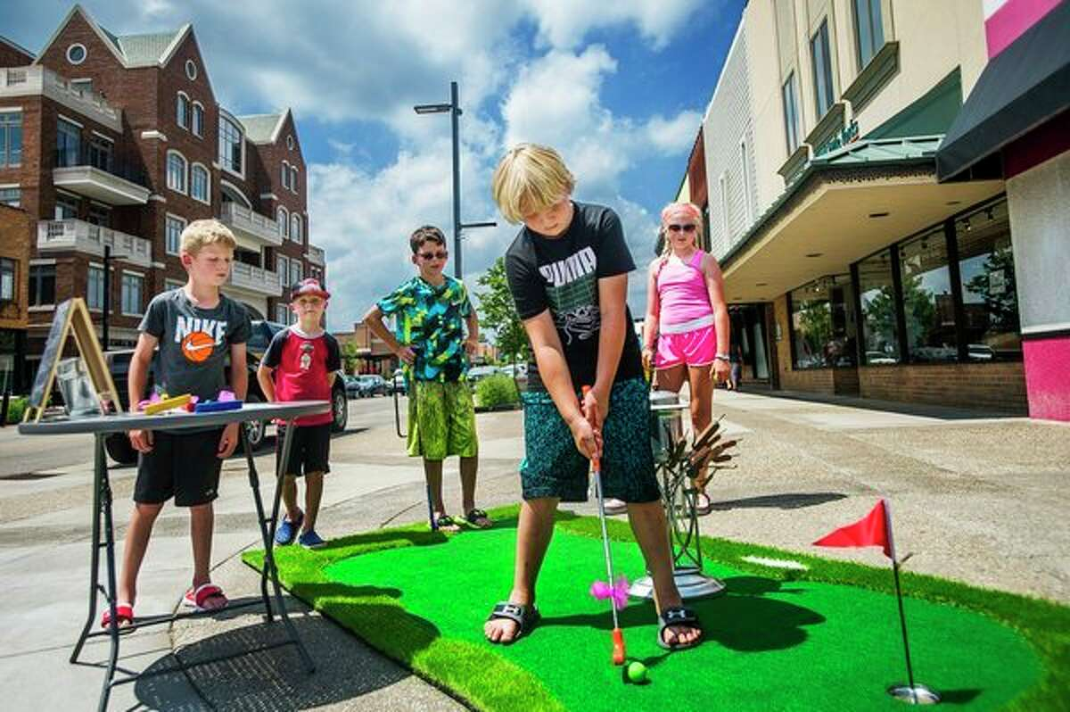 Grady Arnold, 7, lines up a putt while (from left) Evan Baczewski, 8, Keegan Arnold, 6, Erick Baczewski, 11, and Elee Arnold, 9, watch as the group plays mini golf on Wednesday in downtown Midland. Mini Golf on Main, hosted by the Midland Downtown Business Association, will continue through this Saturday, July 13. For more photos, go to www.ourmidland.com. (Katy Kildee/kkildee@mdn.net)