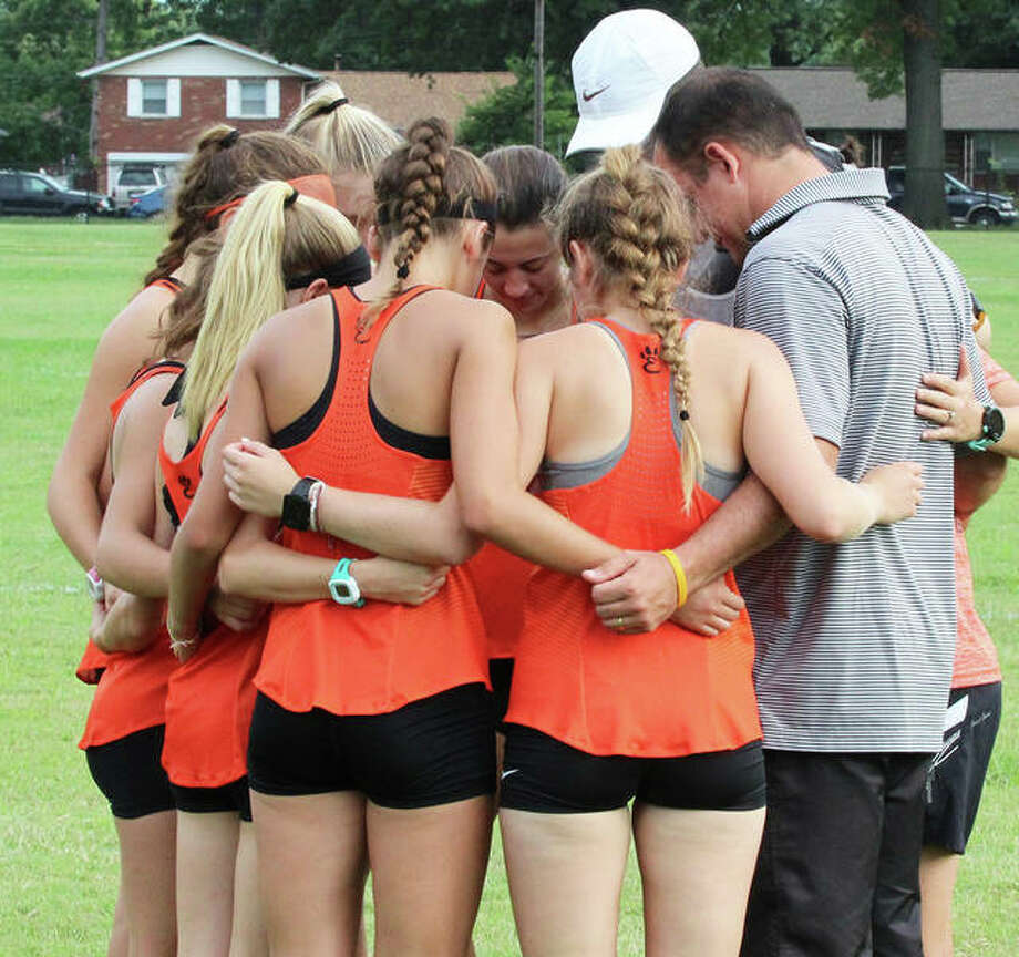 Edwardsville coach George Patrylak (right) huddles with his Tigers girls cross country team for a pre-race prayer before the Granite City Invite on Sept. 1.