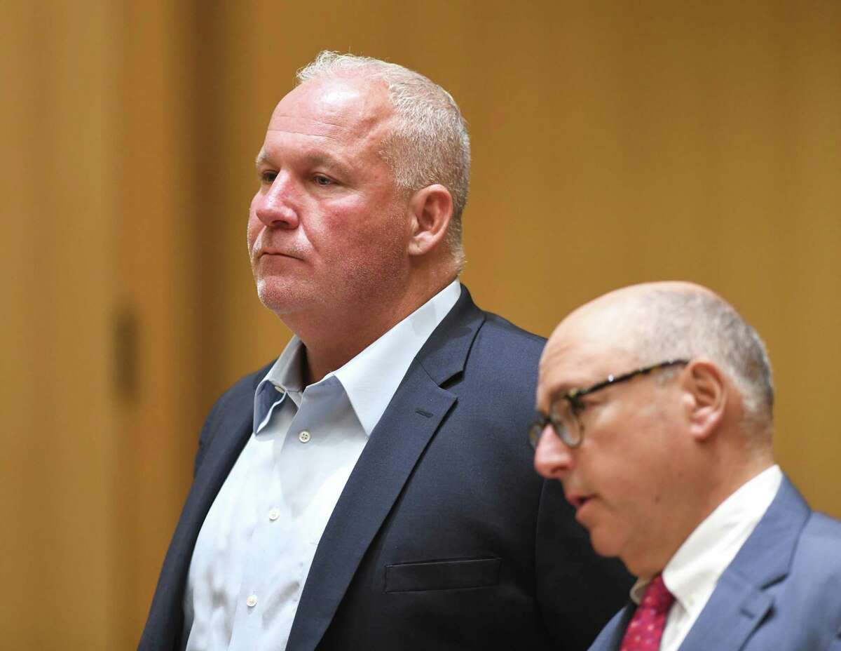 Former Stamford police officer Chris Broems, left, is arraigned and accompanied by his attorney, Philip Russell, for a first-degree larceny charge at the Connecticut Superior Court in Stamford, Conn. Monday, June 24, 2019. Former Stamford police officers Chris Broems, Mark Ligi, Paul Pavia and Dave Sileo were arraigned Monday on first-degree larceny charges for allegedly submitting 643 false payroll vouchers totaling $187,618.