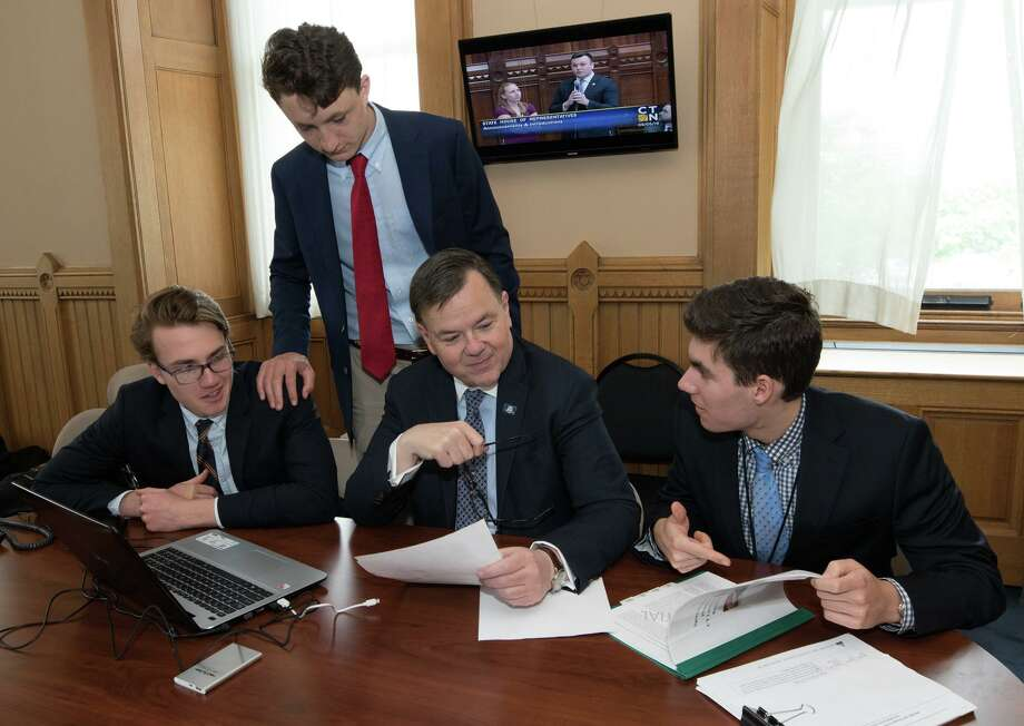 Ridgefield residents Chris Flynn, Miles Tullo and Alec Pool with State. Rep. John Frey. Petros Papadopoulos and Nicholas Patterson also worked as interns for Frey on a research project stretching back to 1776. Photo: Contributed Photo /