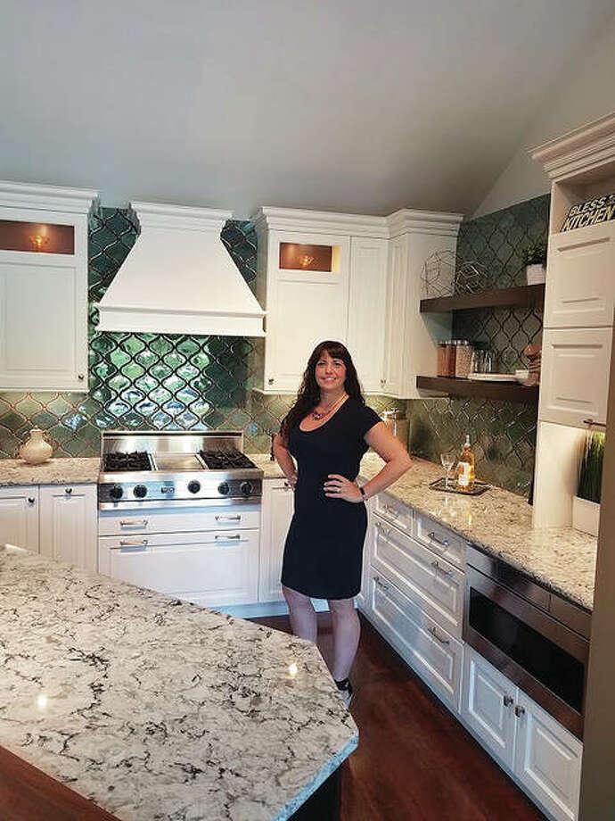 Nationally recognized interior designer Ashleigh Schroeder, of Godfrey, Illinois, with National Kitchen & Bath Inc., stands in a kitchen designed by her, displayed in the company's showroom in Webster Groves, Missouri. Schroeder, 38, is in the process of becoming the business' owner. Photo: For The Edge