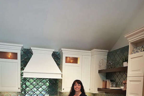 Nationally recognized interior designer Ashleigh Schroeder, of Godfrey, Illinois, with National Kitchen & Bath Inc., stands in a kitchen designed by her, displayed in the company's showroom in Webster Groves, Missouri. Schroeder, 38, is in the process of becoming the business' owner.