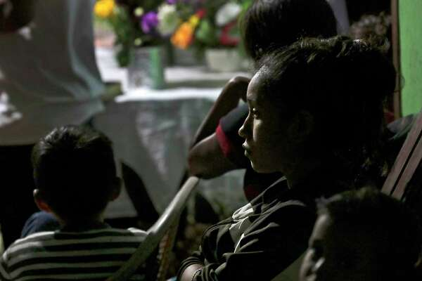 Yulissa Chicas, 24-year-old sister of Briseyda Chicas, sits with family members during a June 30 service at her home in Chiquirines, Guatemala.