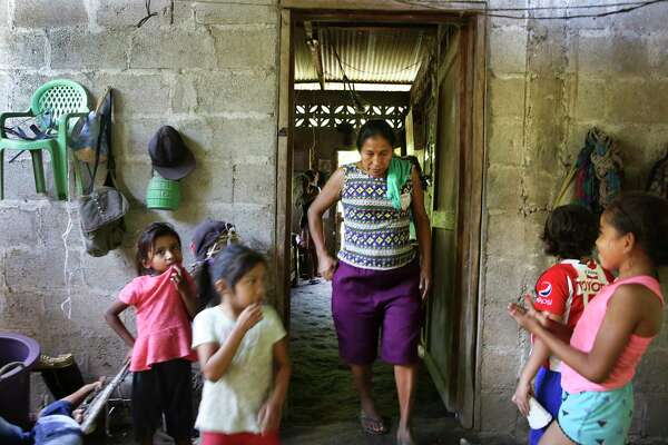 Amalia Perez, mother of Briseyda Chicas, walks past some of her grandchildren.
