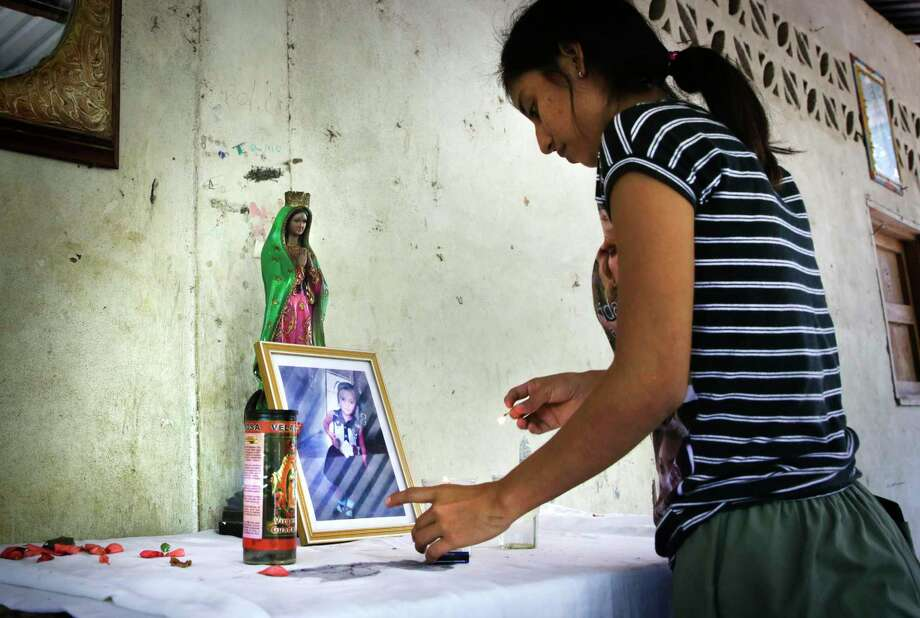 Vivian Aguilar, 20, aunt of Juana Anastasia, 3, from Valle Lirio, Guatemala, lights a candle at a small shrine for the toddler. / ©2019 San Antonio Express-News