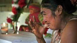 Amelia Sopón, 42, grandmother of Marleny, grieves the death of her granddaughter by a small shrine at her home in El Reparo, Guatemala.