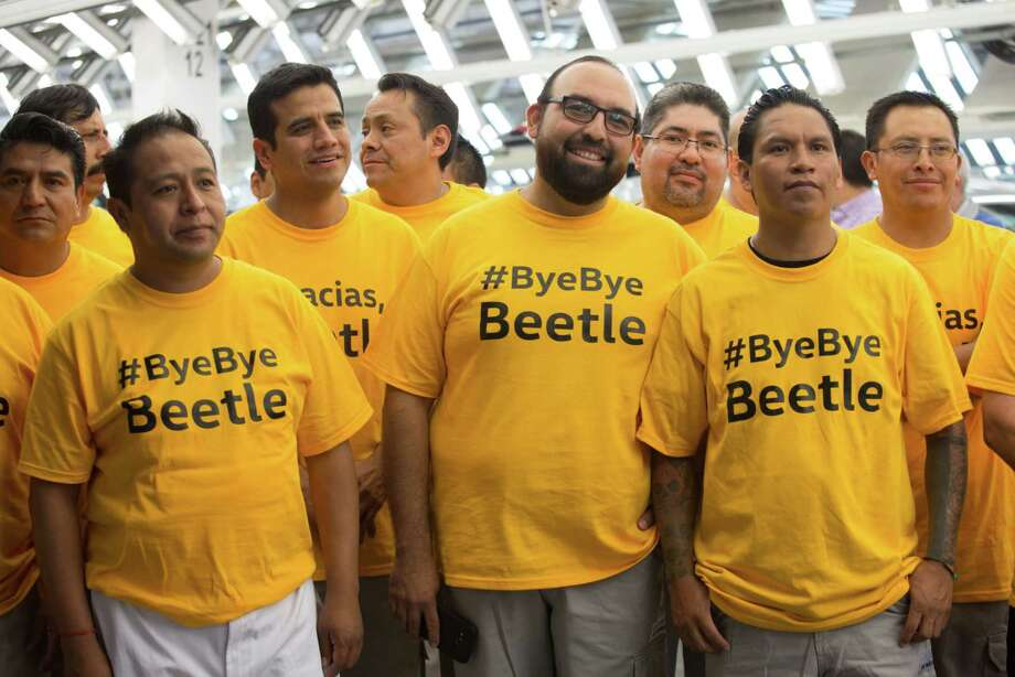 "Employees wear T-shirts reading ""#ByeByeBeetle"" during the Volkswagen Beetle end of production celebration in Puebla, Mexico, on July 10, 2019. Photo: Bloomberg Photo By Alicia Vera. / © 2019 Bloomberg Finance LP"