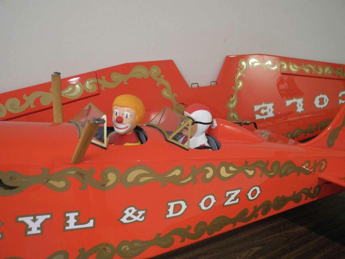 A circus plane features a clown as a co-pilot.