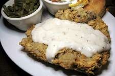 Chicken-fried steak comes with cream gravy, biscuits and sides like green beans and loaded mashed potatoes at Tejas Steakhouse & Saloon.