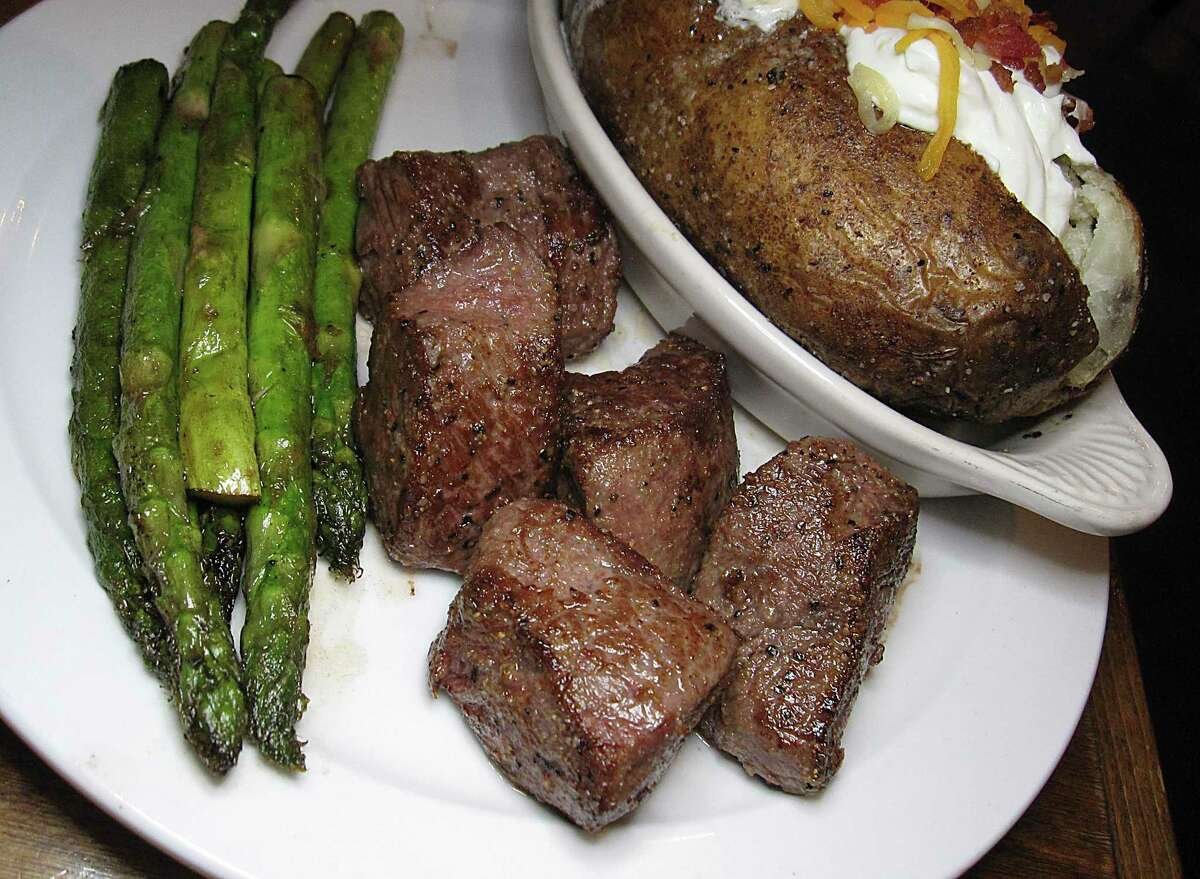 KC Style Steak is a culotte cut of beef served in 2-ounce chunks with sides like asparagus and a loaded baked potato at Tejas Steakhouse & Saloon.