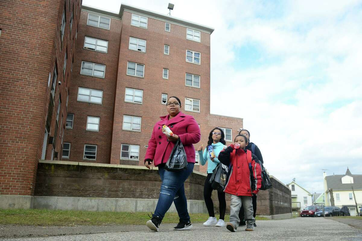 A family walks through the Charles F. Greene homes, in Bridgeport, Conn. Dec. 17, 2018. On Monday the City of Bridgeport announced new efforts to clean and maintain the aging housing complex.