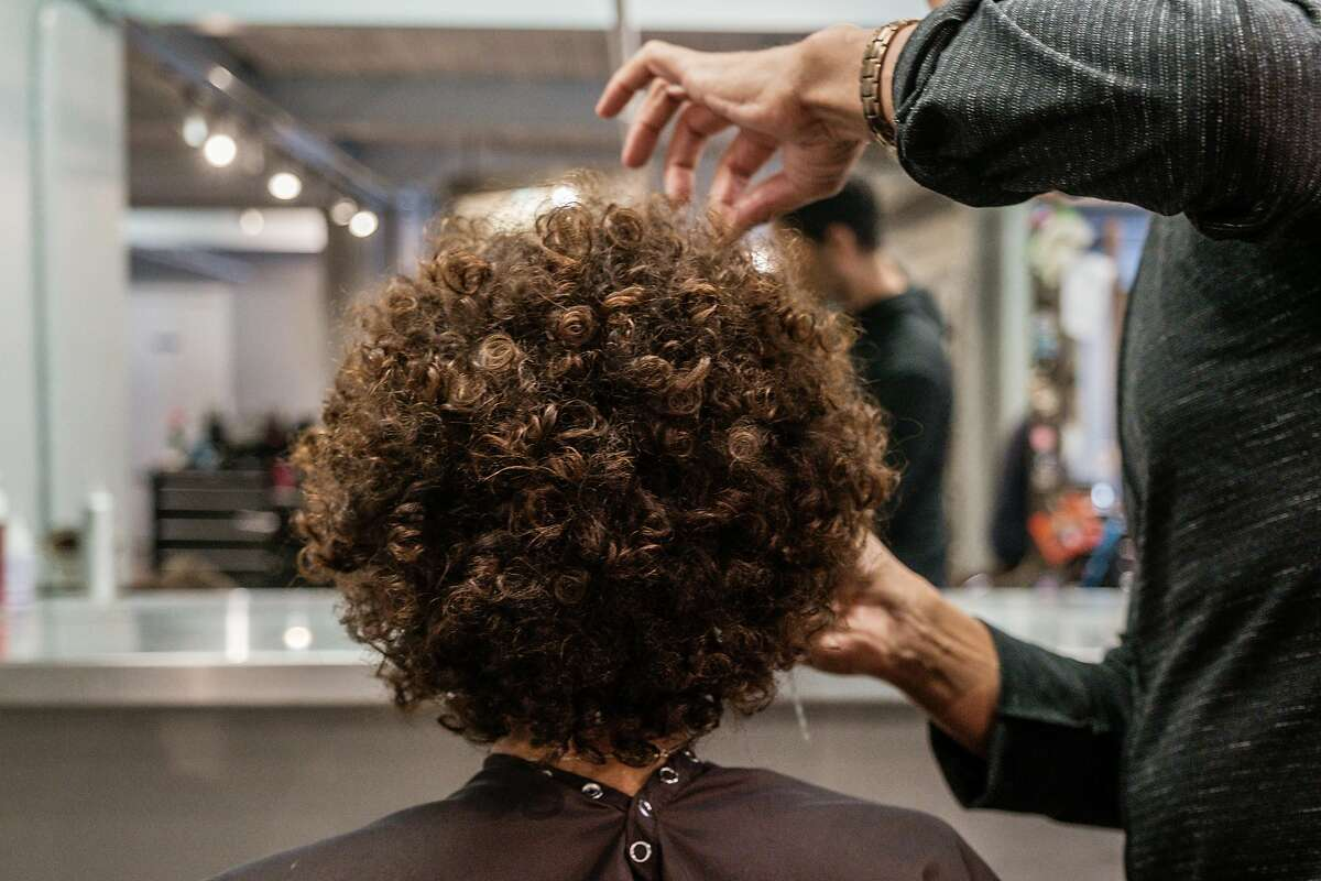 July 3, 2019 -Hair stylist Fritz Clay works on Sherri McMullen's hair at the Hair Play Salon in San Francisco. Gov. Gavin Newsom has signed a bill made California the first state to prohibit discrimination against black employees and students who wear natural hair styles.