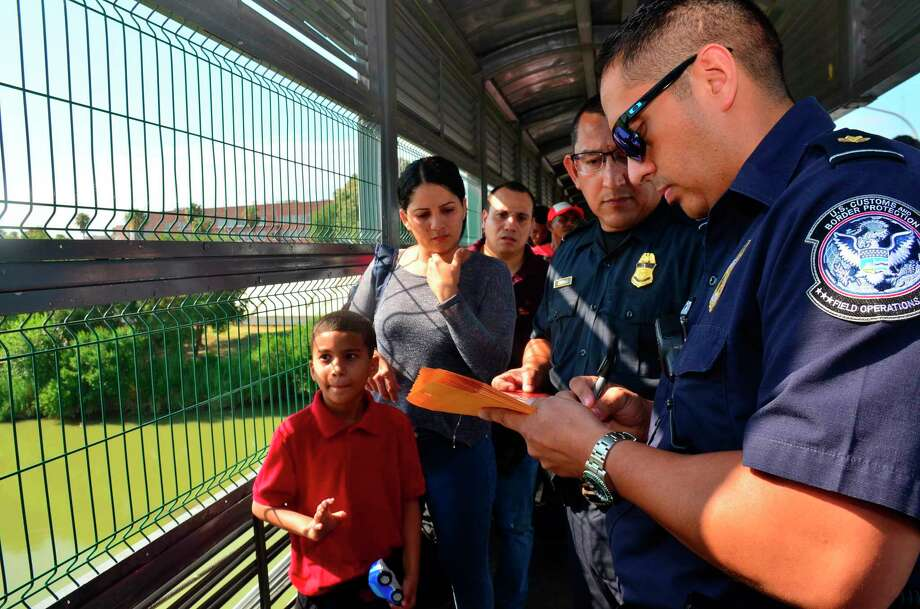 U.S. Customs and Border Patrol agents process a Cuban family, whose turn had been called to cross into the U.S. and apply for asylum, on an international bridge between Nuevo Laredo, Mexico, and Laredo, Texas, Wednesday, July 10, 2019. Photo: Salvador Gonzalez / Associated Press / SALVADOR GONZALEZ