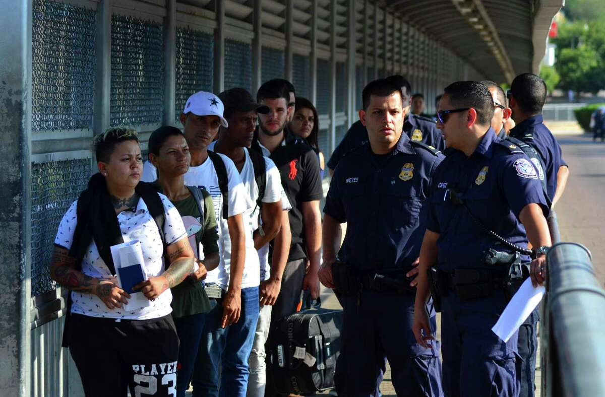 U.S. Customs and Border Patrol officials wait to hand a group of asylum-seekers over to Mexican migration officials as they are returned to Mexico under the so-called Remain in Mexico program, on the international bridge between Laredo, Texas, and Nuevo Laredo, Mexico, Wednesday, July 10, 2019.