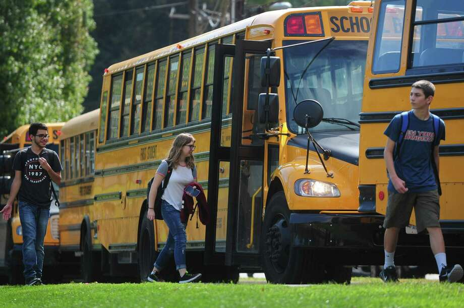 Norwalk High School students catch their First Student buses after school in this file photo from Sept. 15, 2017. The Norwalk Board of Education advocates a later school start time for high school students for health reasons. Photo: Erik Trautmann / Hearst Connecticut Media / Norwalk Hour